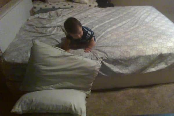 Genius-baby-uses-pillows-for-a-soft-landing-in-bed-dismount