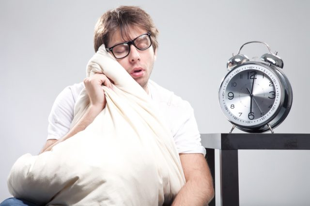 Sleeping man with big clock