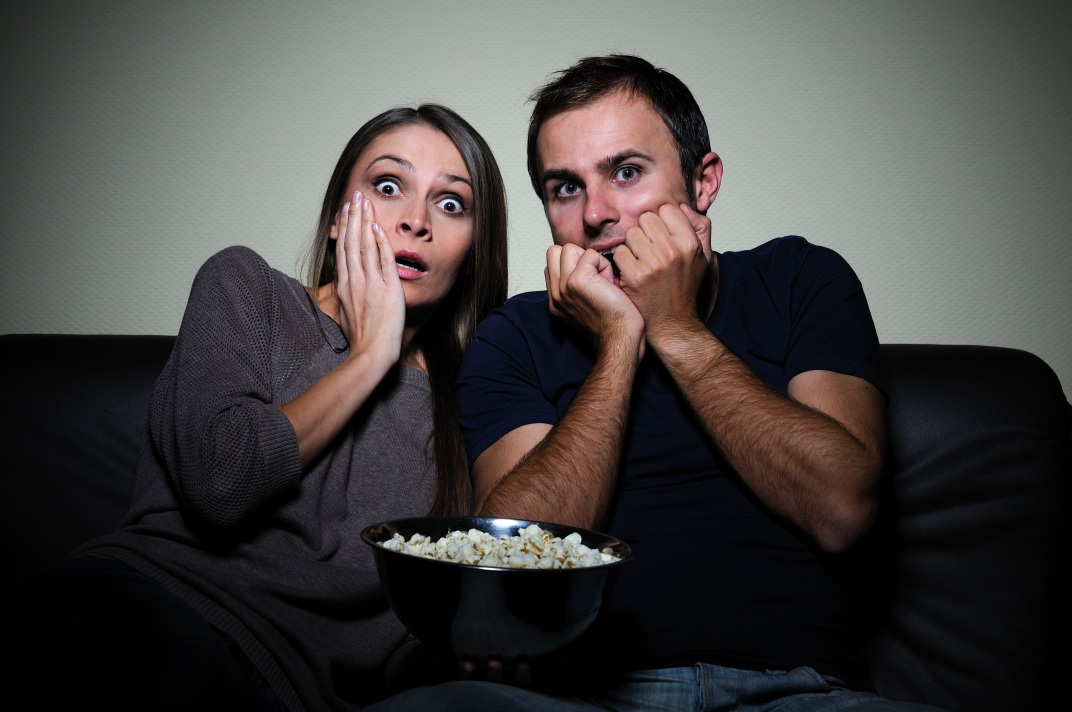 Young couple watching scary movie on tv