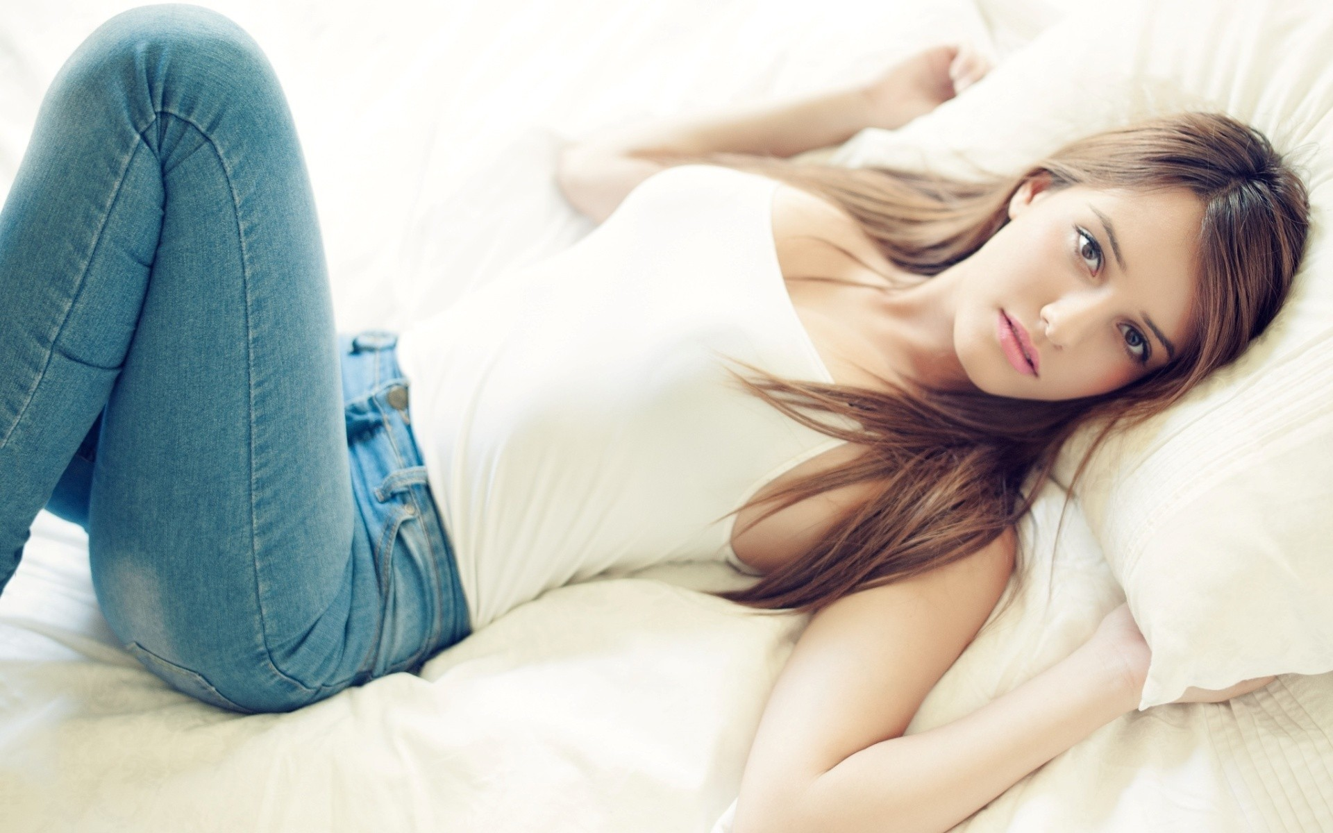 www.GetBg.net_Girls_Girl_in_jeans_and_a_white_tank_top_lying_on_pillows_in_bed_101897_