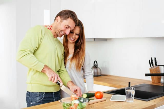 Young pregnant couple cooking together
