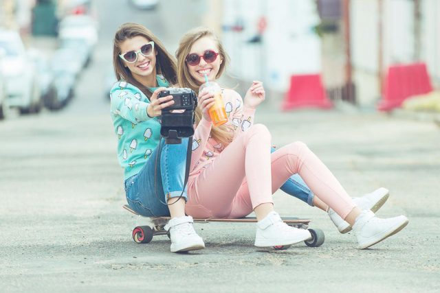 Hipster girlfriends taking a selfie in urban city context - Conc