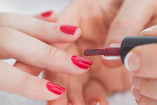 Details shot of hands applying red nail varnish to nails