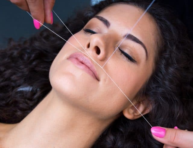 attractive woman in beauty salon on facial hair removal threading procedure
